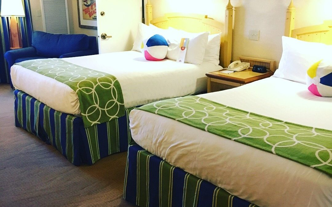 two queen beds with white spread and green throw